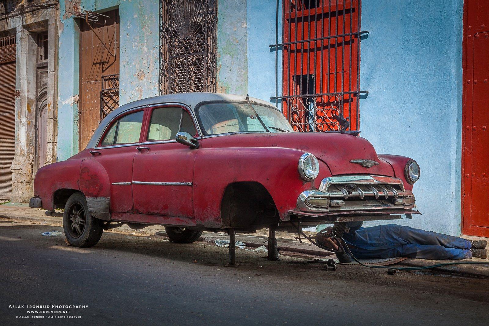 A man lays under a car holding a mechanical work tool.