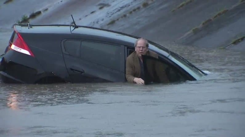 guy escaping from car under water