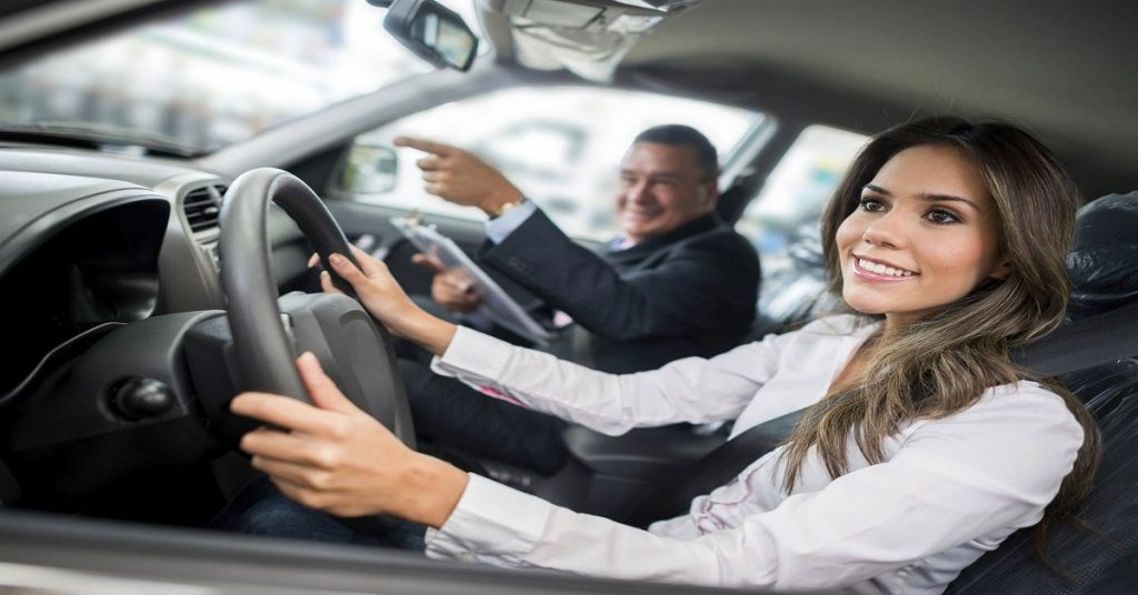 woman test driving a car with accompany of the salesman
